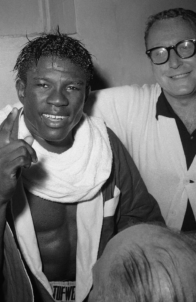 In this June 8, 1963 file photo, Emile Griffith smiles in the dressing room after regaining his welterweight world championship title by defeating Luis Rodriguez, at New York's Madison Square Garden. At right is Griffith's coach, Gil Clancy. Griffith and fellow boxer Ken Norton were among the notables in sports who died in 2013