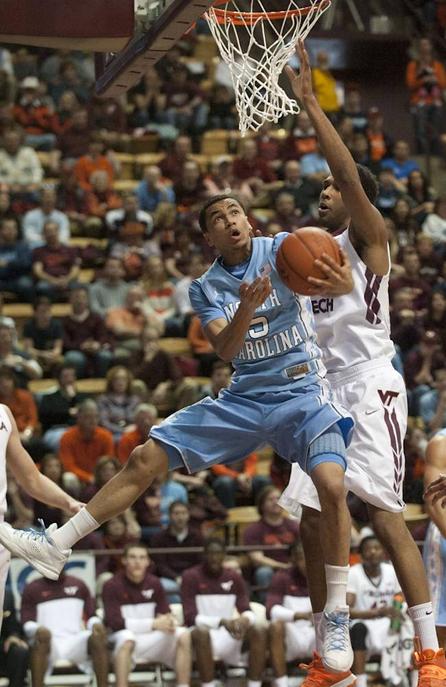 North Carolina's  Marcus Paige (5) goes up against Virginia Tech's Trevor Thompson during the first half of an NCAA college basketball game,  Saturday, March 1, 2014, in Blacksburg, Va