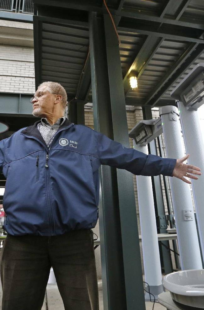 Seattle Mariners employee Chuck Viltz stands as he is checked with a hand-held metal detector after walking through a magnetometer, at right, during a demonstration of new entrance security measures at the team's ballpark, Tuesday, Jan. 21, 2014, in Seattle. During the demonstration, Viltz was