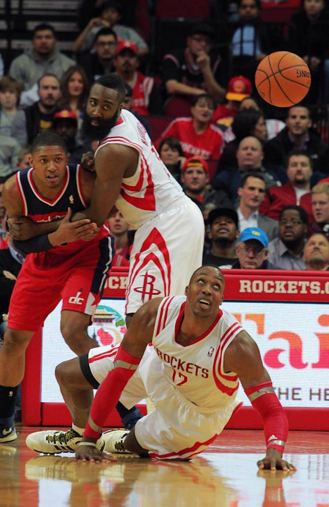 Houston Rockets center Dwight Howard, bottom, watches a loose ball as teammate James Harden, center, holds back Washington Wizards guard Bradley Beal, left, during the second half of an NBA basketball game in Houston, Wednesday, Feb. 12, 2014