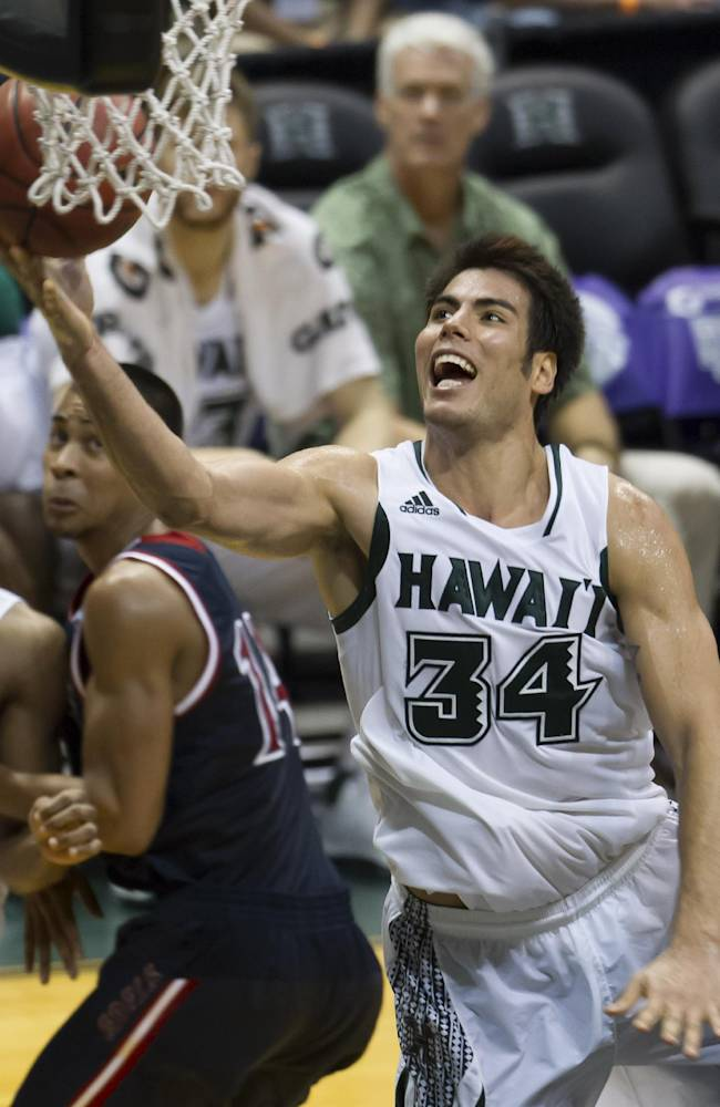 Hawaii forward Christian Standhardinger (34) shoots a layup as St. Mary's guard Stephen Holt, left, looks on in the second half of an NCAA college basketball game at the Diamond Head Classic Monday, Dec. 23, 2013, in Honolulu. Hawaii beat Saint Mary's 76-74