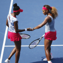 Venus Williams and Serena Williams slap hands between points against Garbine Muguruza and Carla Suarez Navarro, of Spain, during a doubles match at the 2014 U.S. Open tennis tournament, Sunday, Aug. 31, 2014, in New York. (AP Photo/Seth Wenig)