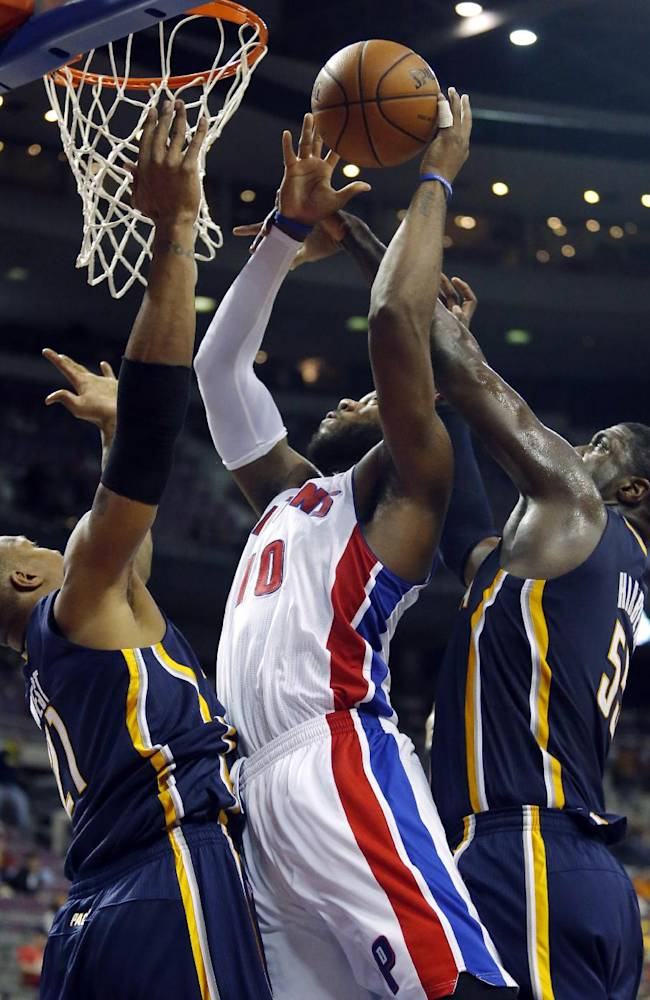 Detroit Pistons center Greg Monroe (10) goes to the basket between Indiana Pacers forward David West (21) and center Roy Hibbert (55) during the second half of an NBA basketball game Tuesday, Nov. 5, 2013, in Auburn Hills, Mich
