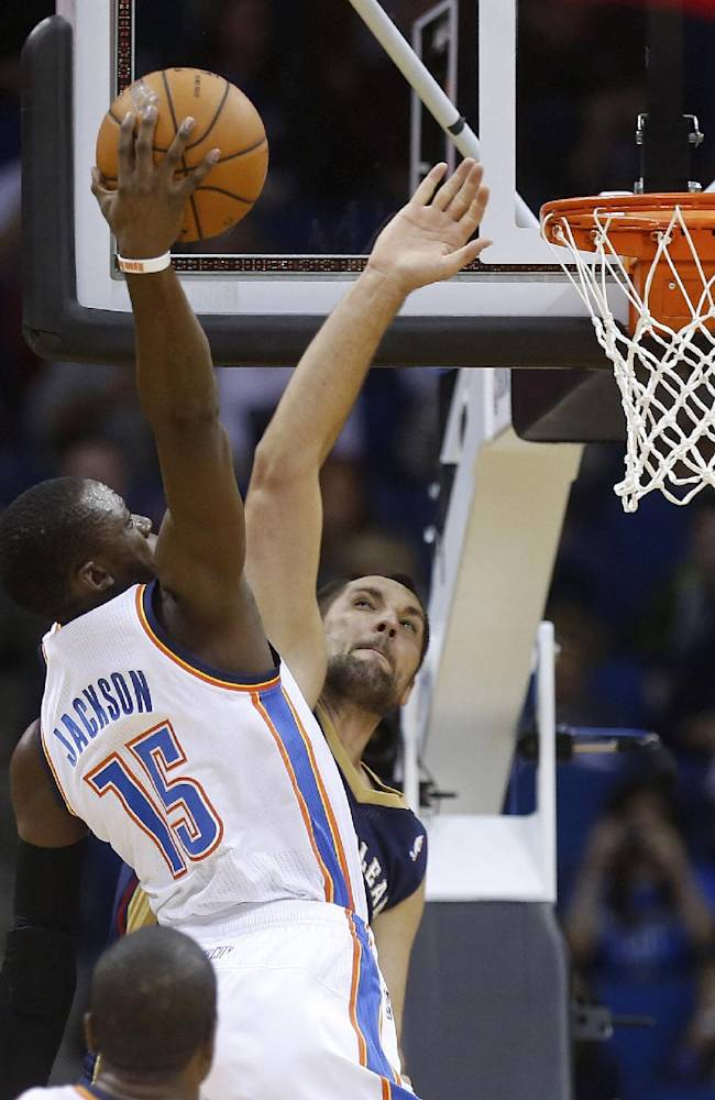 Oklahoma City Thunder guard Reggie Jackson (15) goes up for a dunk in front of New Orleans Pelicans forward Ryan Anderson during the first quarter of an NBA basketball preseason game in Tulsa, Okla., Thursday, Oct. 17, 2013