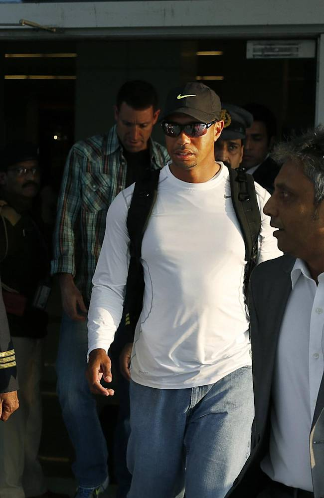 Tiger Woods, center, arrives at the Indira Gandhi International airport in New Delhi, India, Monday, Feb. 3, 2014. Woods arrived Monday on his first visit to India to play an exhibition with a top business executive. (AP Photo /Manish Swarup)