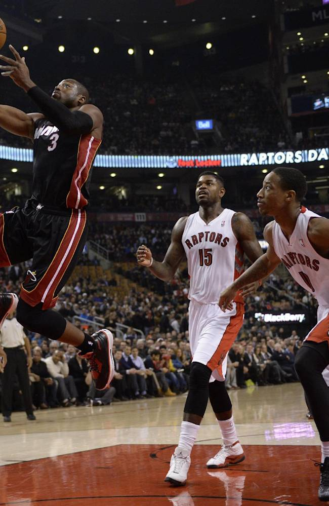 Miami Heat's Dwyane Wade drives to the basket as Toronto Raptors defend during the first half of an NBA basketball game, Tuesday, Nov. 5, 2013 in Toronto