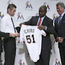 Ichiro Suzuki, second left, is handed Miami Marlins' uniform by Michael Hill, second right, president of Marlins' baseball operations, as Marlins President David Samson, left, and Dan Jennings, right, team's general manager, accompany him during a news co