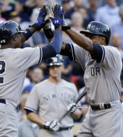 New York Yankees' Curtis Granderson , right, and Alfonso Soriano high five after Granderson's two-run home run against the San Diego Padres in the seventh inning of an interleague baseball game in San Diego, Saturday, Aug. 3, 2013. (AP Photo/Lenny Ignelzi)