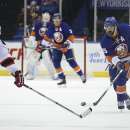 New York Islanders right wing Cal Clutterbuck (15) skates the puck upice against New Jersey Devils center Adam Henrique (14) in the second period of an NHL hockey game on Saturday, March 29, 2014, in Uniondale, N.Y The Associated Press