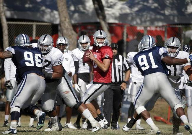 Oakland Raiders quarterback Matt Schaub, center, looks to pass during the team's joint football practice with the Dallas Cowboys on Tuesday, Aug. 12, 2014, in Oxnard, Calif