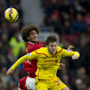 Manchester United's Marouane Fellaini, left, fights for the ball against Liverpool's Adam Lallana during the English Premier League soccer match between Manchester United and Liverpool at Old Trafford Stadium, Manchester, England, Sunday Dec. 14, 2014