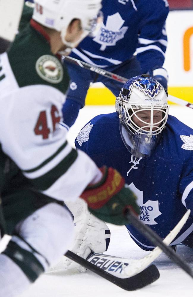 Toronto Maple Leafs goaltender James Reimer makes a save under heavy pressure from the Minnesota Wild during the third period of an NHL hockey game in Toronto on Tuesday, Oct. 15, 2013. Toronto won 4-1