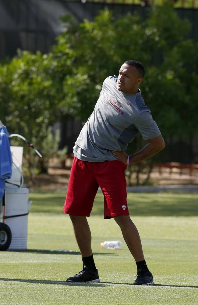 From left to right, Arizona Cardinals' Marcus Benard, Michael Floyd and Antonio Cromartie stretch during the first phase of the voluntary offseason training program at the NFL football team's training facility on Thursday, April 24, 2014, in Tempe, Ariz