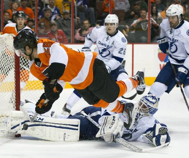 Philadelphia Flyers' Claude Giroux, top, shoots the puck at Tampa Bay Lightning's Anders Lindback, bottom, of Sweden, who makes a pad save during the second period of an NHL hockey game, Saturday, Jan. 11, 2014, in Philadelphia