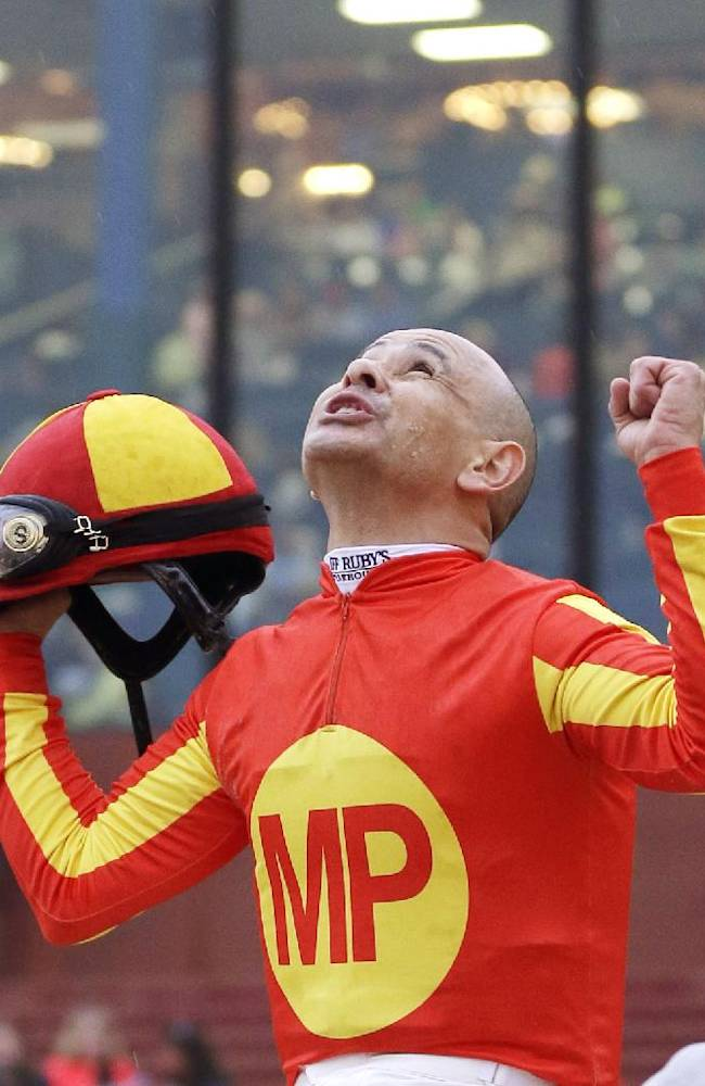 Jockey Mike Smith gestures skyward as he and Hoppertunity are led to the winners circle after winning the $600,000 Rebel Stakes horse race at Oaklawn Park in Hot Springs, Ark., Saturday, March 15, 2014