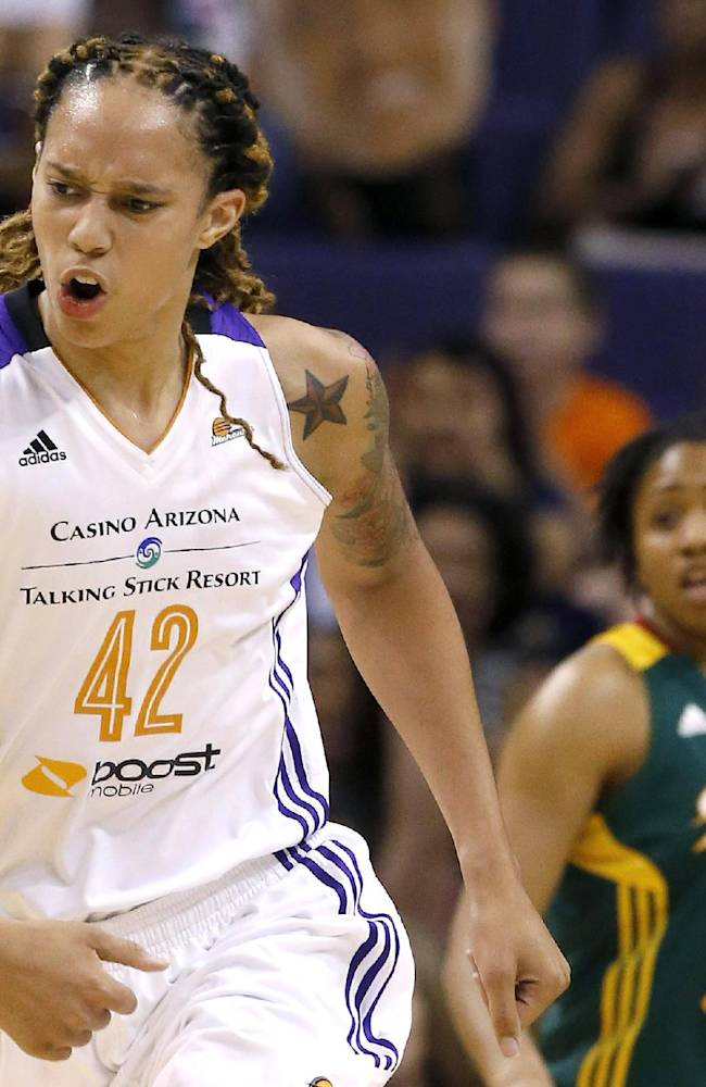 Phoenix Mercury's Brittney Griner (42) shouts in celebration after scoring as Seattle Storm's Tanisha Wright (30) looks on during the first half of a WNBA basketball game on Tuesday, June 3, 2014, in Phoenix