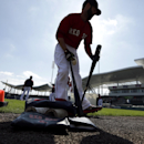 Boston Red Sox second baseman Dustin Pedroia holds two bats as he steps onto the field to warm up before an exhibition baseball game against the Minnesota Twins, Friday, Feb. 28, 2014, in Fort Myers, Fla The Associated Press