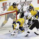 Pittsburgh Penguins center Sidney Crosby, top center, scores a goal against Nashville Predators goalie Pekka Rinne (35), of Finland, in the first period of an NHL hockey game Saturday, Oct. 25, 2014, in Nashville, Tenn. (AP Photo/Mark Humphrey)