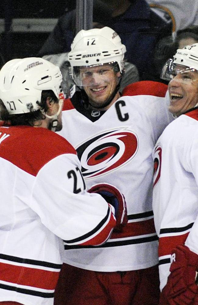 Carolina Hurricanes' Justin Faulk (27), and Alexander Semin (28), celebrate a goal by Eric Staal, center, during the second period of an NHL hockey game against the Buffalo Sabres in Buffalo, N.Y., Tuesday, Feb. 25, 2014