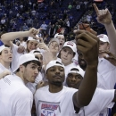 Doug McDermott, center, and several players from Creighton pose for a photo after beating Wichita State 68-65 for the Missouri Valley Conference tournament championship, in an NCAA college basketball game Sunday, March 10, 2013 in St. Louis. McDermott was named tournament Most Valuable Player.(AP Photo/Tom Gannam)