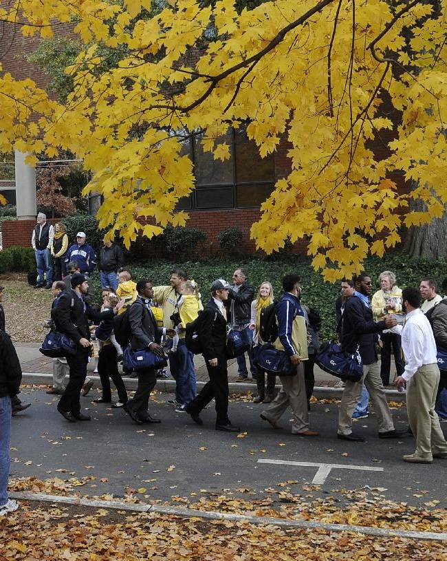 Georgia Tech players walk down Yellow Jacket Alley past fans on the way to the stadium to play Alabama A&M in an NCAA college football game, Saturday, Nov. 23, 2013, in Atlanta