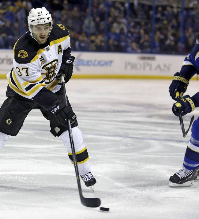 Boston Bruins' Patrice Bergeron, left, handles the puck as St. Louis Blues' Alexander Steen watches during the first period of an NHL hockey game Thursday, Feb. 6, 2014, in St. Louis