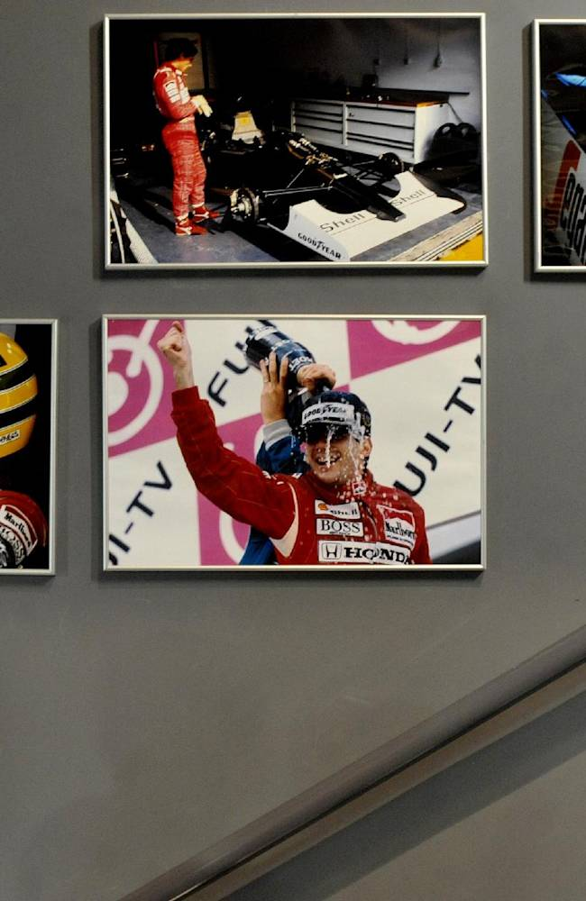 A man looks at pictures showing late Brazilian F1 driver Ayrton Senna, on display at the the Imola track, Italy, Wednesday, April 30, 2014. Fans and family members are gathering this week to pay their respects to former Formula One drivers Ayrton Senna and Roland Ratzenberger on the 20th anniversary of their deaths. F1 drivers' chaplain Sergio Mantovani celebrated a memorial mass Wednesday in a packed room beside pit lane at the Enzo and Dino Ferrari track that once hosted the San Marino Grand Prix