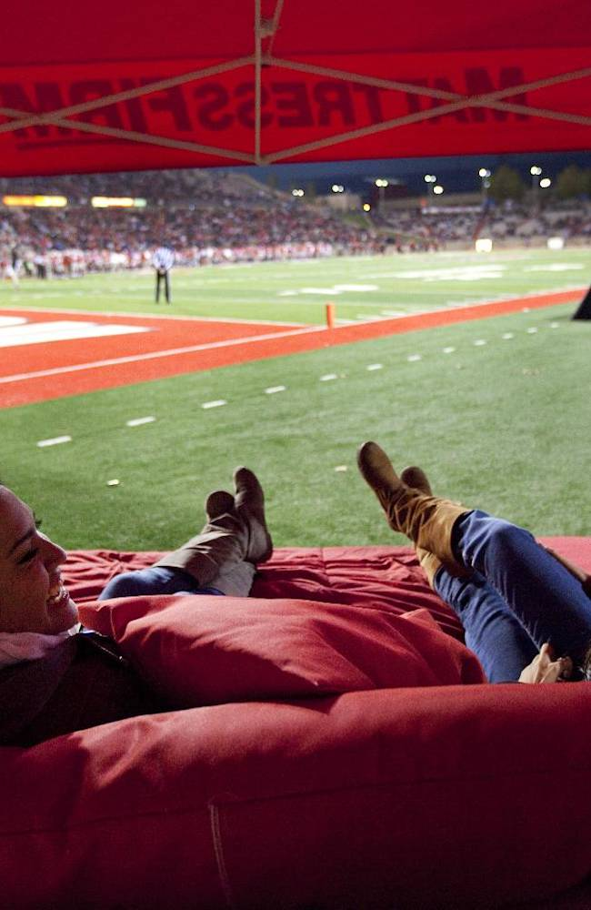 New Mexico football fans Martha Mendoza, right, and Samantha Chavez enjoy the action from a mattress on the sideline in the first half of an NCAA college football game against Colorado State on Saturday, Nov. 16, 2013 in Albuquerque, N.M. Colorado State won 66-42