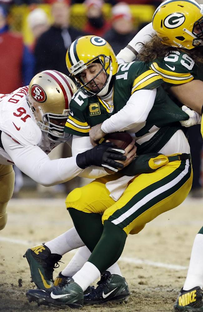 San Francisco 49ers defensive end Ray McDonald (91) tackles Green Bay Packers quarterback Aaron Rodgers (12) as the 49ers outside linebacker Aldon Smith, right, grabs Rodgers while fighting against the Packers offensive tackle David Bakhtiari (69) during the first half of an NFL wild-card playoff football game, Sunday, Jan. 5, 2014, in Green Bay, Wis
