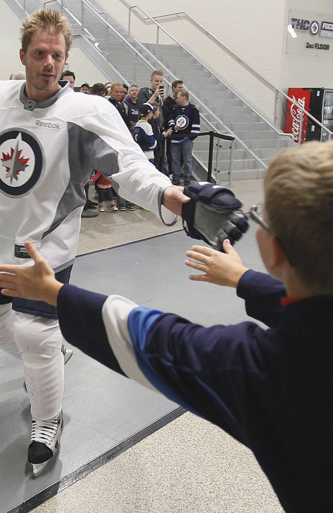 Winnipeg Jets' Ian White (7) reaches out to a young fan at NHL hockey training camp Thursday, Sept. 12, 2013, in Winnipeg, Manitoba