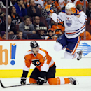 Edmonton Oilers' Taylor Hall, right, leaps to avoid Philadelphia Flyers' Luke Schenn, left, during the first period of an NHL hockey game, Saturday, Nov. 9, 2013, in Philadelphia The Associated Press