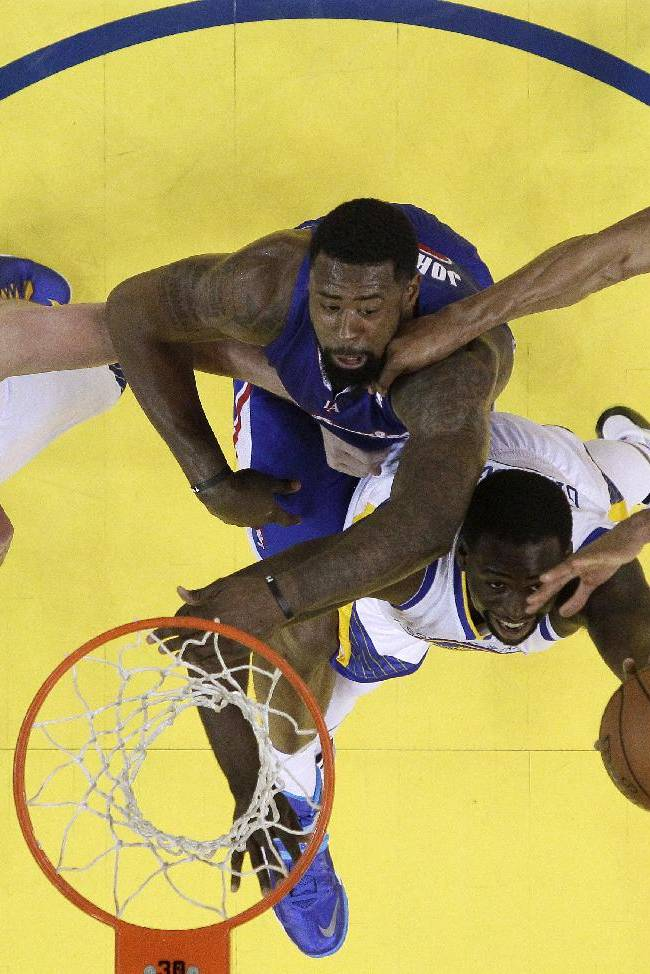 CORRECTS BYLINE - Los Angeles Clippers' DeAndre Jordan, center in blue, battles for a rebound against Golden State Warriors' David Lee, left, Draymond Green, bottom center, and Andre Iguodala, right, during the first half in Game 3 of an opening-round NBA basketball playoff series on Thursday, April 24, 2014, in Oakland, Calif. Los Angeles won 98-96