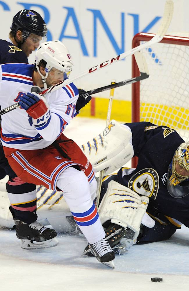 St. Louis Blues' goalie Jaroslav Halak (41), of Slovakia, and Alex Pietrangelo, back left, block a shot by New York Rangers' Benoit Pouliot (67) during the third period of an NHL hockey game on Saturday, Oct. 12, 2013, in St. Louis