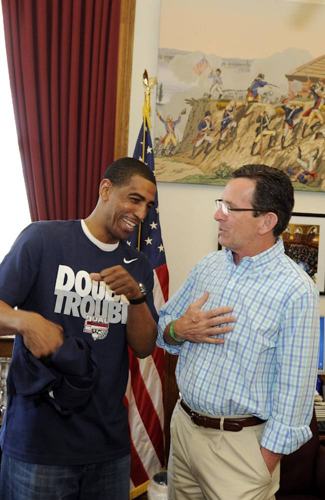 Connecticut coach Kevin Ollie, left, talks with Connecticut Gov. Dannel P. Malloy in his office on Sunday, April 13, 2014, in Hartford, Conn., to celebrate UConn men's and women's NCAA college basketball championships. AP Photo/Fred Beckham)