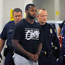 In this Sept. 17, 2014, file photo, Phoenix police officers escort Arizona Cardinals running back Jonathan Dwyer, to the 4th Avenue Jail following his arrest in Phoenix. Dwyer is scheduled to be arraigned Monday, Oct. 6, 2014, on charges that he assault