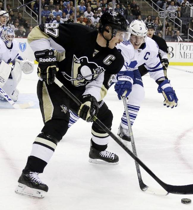 Pittsburgh Penguins' Sidney Crosby (87) works the puck in the corner against Toronto Maple Leafs' Dion Phaneuf during the second period of an NHL hockey game in Pittsburgh, Wednesday, Nov. 27, 2013