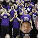 Washington students cheer their team as they hold giant cut-out photos of C.J. Wilcox, left, and head coach Lorenzo Romar against Colorado in the second half of an NCAA men's basketball game Sunday, Jan. 12, 2014, in Seattle. Washington won 71-54. (AP Photo/Elaine Thompson)
