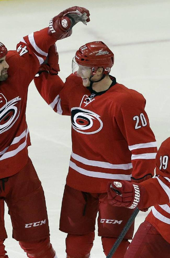 Carolina Hurricanes' Jay Harrison (44), Riley Nash (20) and Jiri Tlusty (19), of the Czech Republic, celebrate Nash's goal against the San Jose Sharks during the third period of an NHL hockey game in Raleigh, N.C., Friday, Dec. 6, 2013. Carolina won 5-3