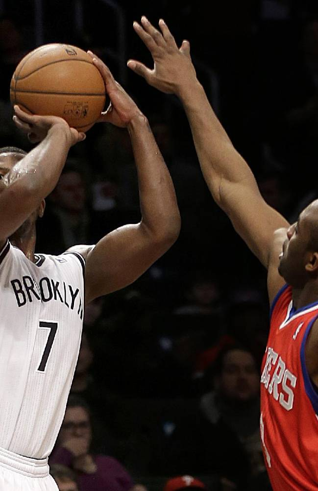 Brooklyn Nets' Joe Johnson, left, takes a shot over Philadelphia 76ers' James Anderson during the first half of an NBA basketball game at the Barclays Center, Monday, Dec. 16, 2013, in New York
