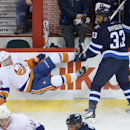 New York Islanders' Thomas Hickey (14) falls to the ice after being checked by Winnipeg Jets' Dustin Byfuglien (33) during the first period of an NHL hockey game in Winnipeg, Manitoba, Tuesday, March 4, 2014 The Associated Press