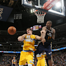 Denver Nuggets center Timofey Mozgov, left, of Russia, passes the ball away from Utah Jazz center Derrick Favors during the fourth quarter of the Nuggets' 101-94 victory in an NBA basketball game in Denver on Saturday, April 12, 2014 The Associated Press