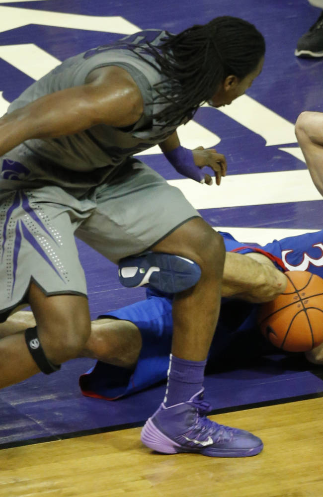 Kansas forward Perry Ellis (34) falls out of bounds while covered by Kansas State forward D.J. Johnson, left, during the second half of an NCAA college basketball game in Manhattan, Kan., Monday, Feb. 10, 2014. Kansas State defeated Kansas 85-82 in overtime
