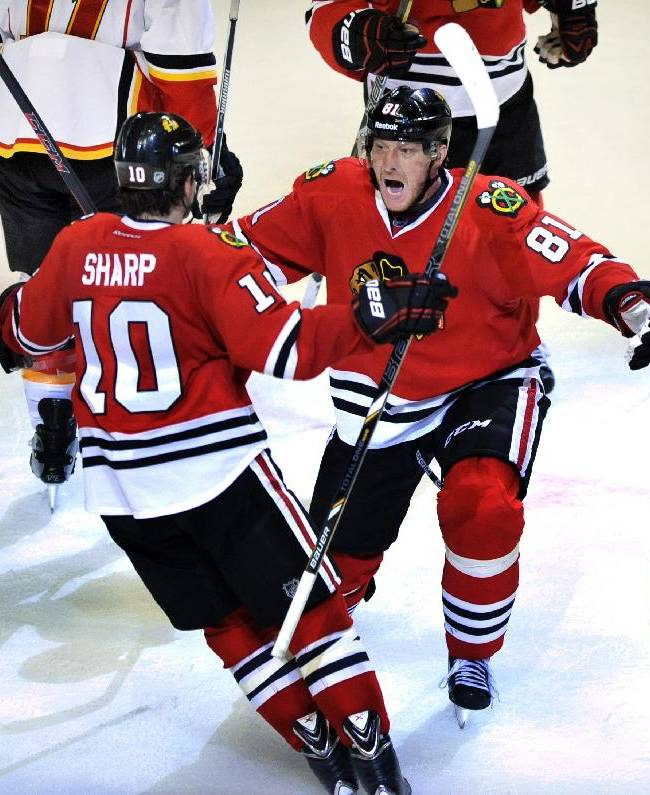 Chicago Blackhawks' Marian Hossa (81), of Slovakia, celebrates with teammate Patrick Sharp (10), during the third period of an NHL hockey game against the Calvary Flames in Chicago, Sunday, Nov. 3, 2013. Calgary won 3-2 in overtime