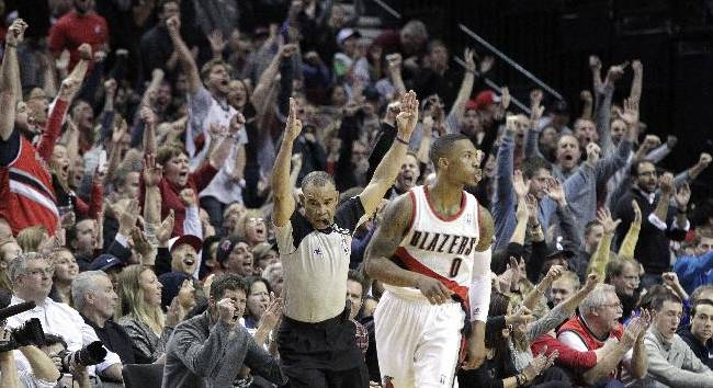 The crowd reacts after Portland Trail Blazers guard Damian Lillard, middle, sinks a three point shot late in the second half of an NBA basketball game against the Indiana Pacers in Portland, Ore., Monday, Dec. 2, 2013.  Lillard scored 26 points as the Trail Blazers won 106-102