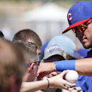 FILE - In this March, 2015, file photo, Chicago Cubs' Kris Bryant signs autographs prior to start of a spring training exhibition baseball game against the San Diego Padres in Peoria, Ariz. Bryant was reassigned by the Cubs to their minor league camp on Monday despite an outstanding spring training at the plate, triggering a threat of litigation from the players' association. (AP Photo/Lenny Ignelzi, File)