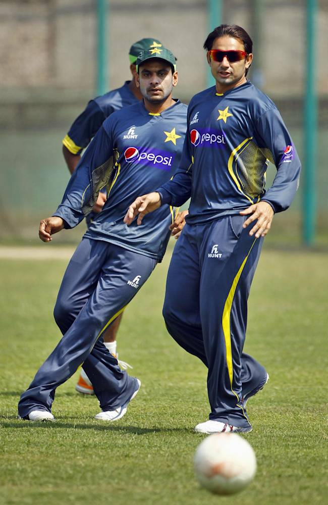Pakistan's Saeed Ajmal, right, and Mohammad Hafeez play with a soccer ball during a team practice session in Dhaka, Bangladesh, Friday, March 7, 2014. Pakistan will face Sri Lanka in the Asia Cup final match on Saturday