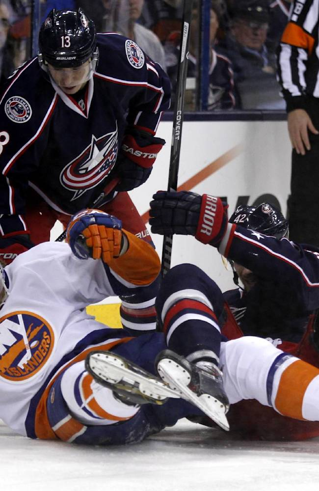 New York Islanders' Anders Lee (27), Columbus Blue Jackets' Cam Atkinson (13) and Artem Anisimov (42), of Russia, work for the puck in the second period of an NHL hockey game in Columbus, Ohio, Sunday, April 6, 2014
