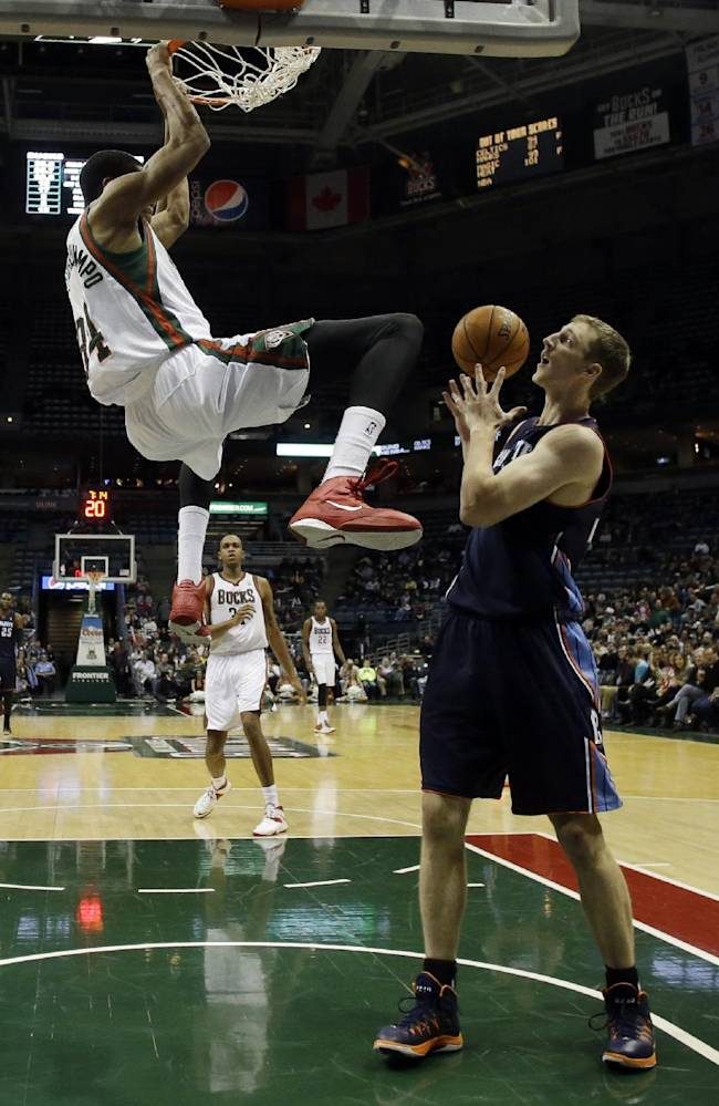 Milwaukee Bucks' Giannis Antetokounmpo, top, dunks over Charlotte Bobcats' Cody Zeller during the second half of an NBA basketball game on Saturday, Nov. 23, 2013, in Milwaukee