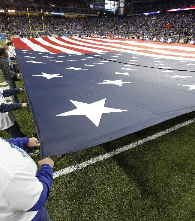Fans hold an American Flag during introductions before an NFL football game between the Detroit Lions and the Green Bay Packers at Ford Field in Detroit, Thursday, Nov. 28, 2013