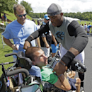 Carolina Panthers' Cam Newton right, gives his shoes to fan Brian Cooper, of Greensville, S.C., bottom, after an NFL football practice at their training camp in Spartanburg, S.C., Monday, July 28, 2014 The Associated Press